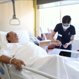 Patient in hospital bed with nurse attaching heart rate monitor