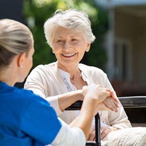 A nurse tends to a woman sat in a wheel chair