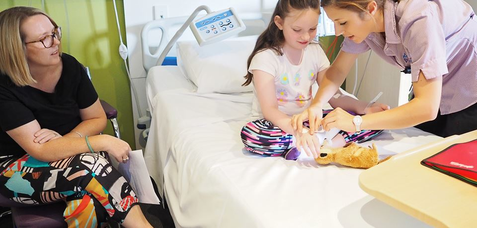 A nurse looks after a young girls in a hospital room