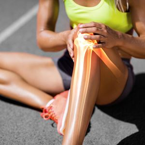 An athlete hold her injured knee