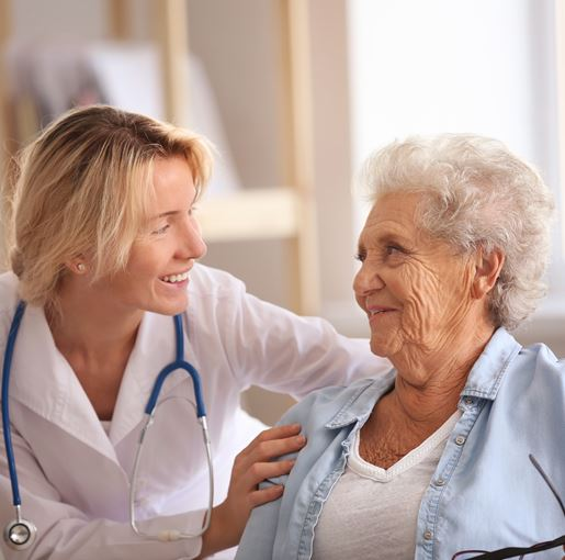 A nurse talks to an elderly man in a wheelchair