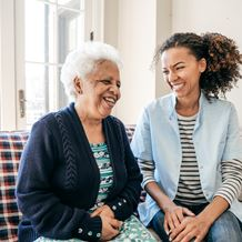 A young woman laughs with an elderly patient